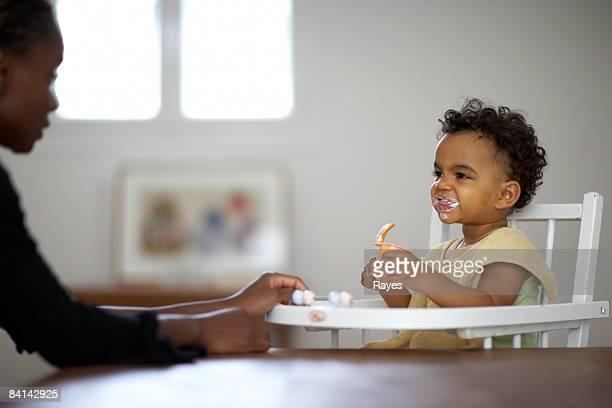 baby feeding himself yoghurt
