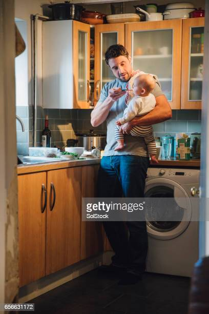 baby feeding time - role reversal stock photos and pictures