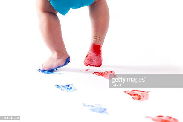 Baby feet leaving blue and red footprints behind