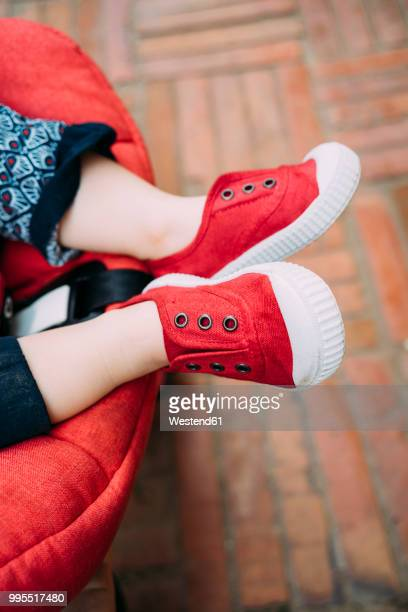 baby feet with red shoes in the stroller - red shoe stock pictures, royalty-free photos & images