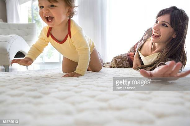 Baby first crawls, mother watches