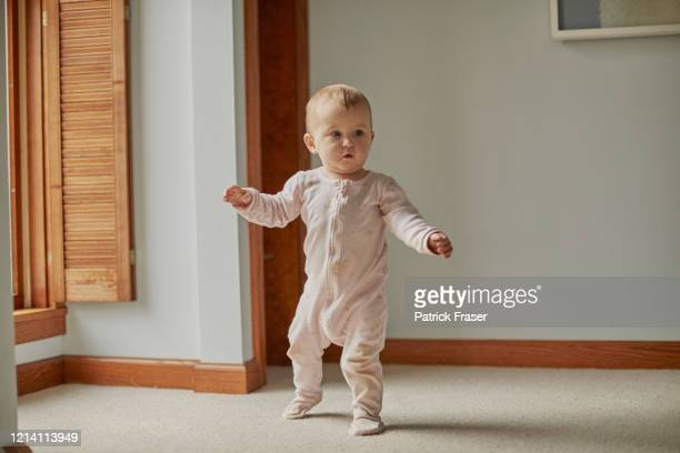 baby first steps walking in bedroom with arms out with good balance - baby stock pictures, royalty-free photos & images