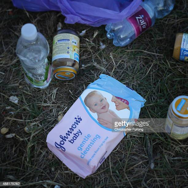 Baby food and baby wipes lay on the ground as migrants discard items no longer wanted or needed when they cross the Hungarian border on September 14...