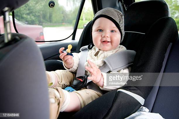 A baby front facing early in car seat and unsafely strapped