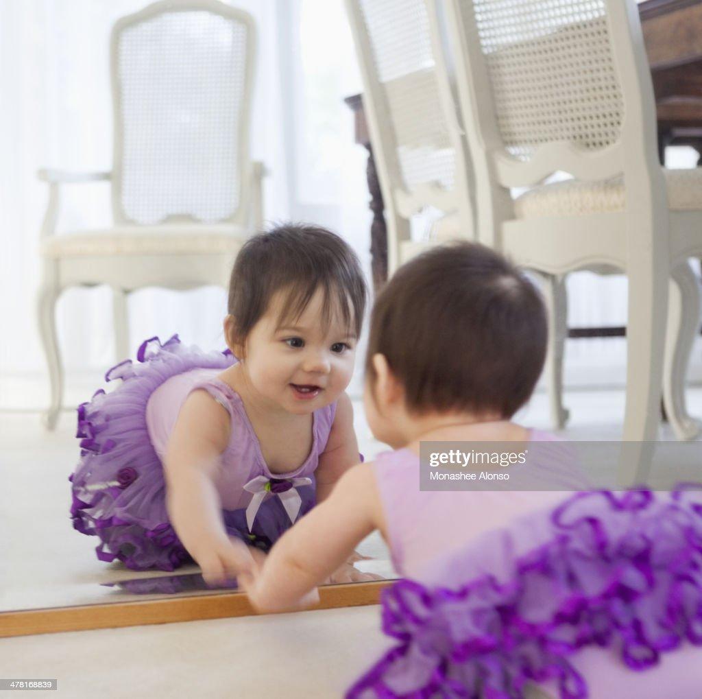 Baby girl admiring herself in mirror : Stock Photo