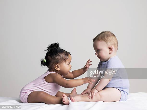 Baby girl and baby boy (6-9 months) playing