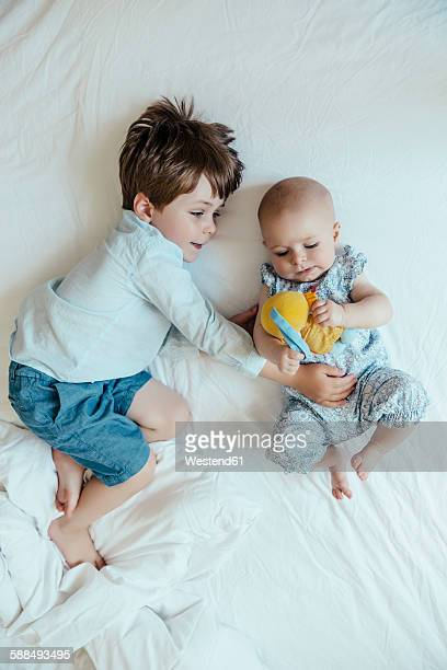 Baby girl and brother lying side by side on bed