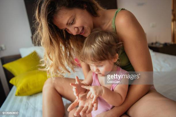 Baby girl and her mother in bed playing together