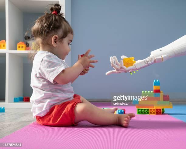baby meisje en robot spelen met speelgoed blokken - cyborg stockfoto's en -beelden