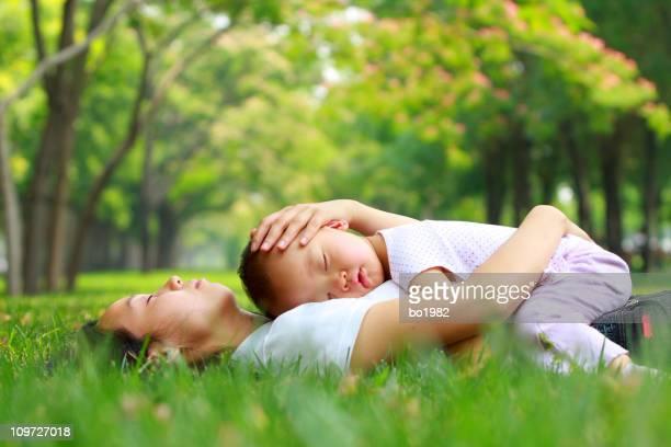 baby girl asleep on mom's chest in the garden