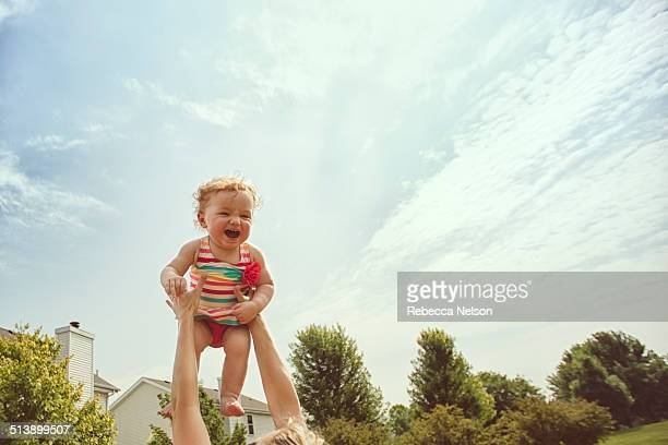 baby girl being thrown up in the air