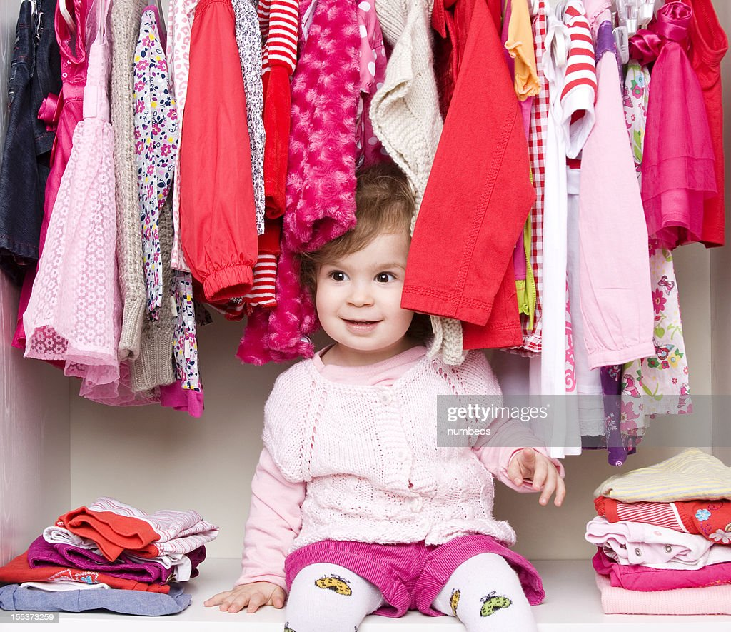 Baby girl choosing her clothes : Stock Photo