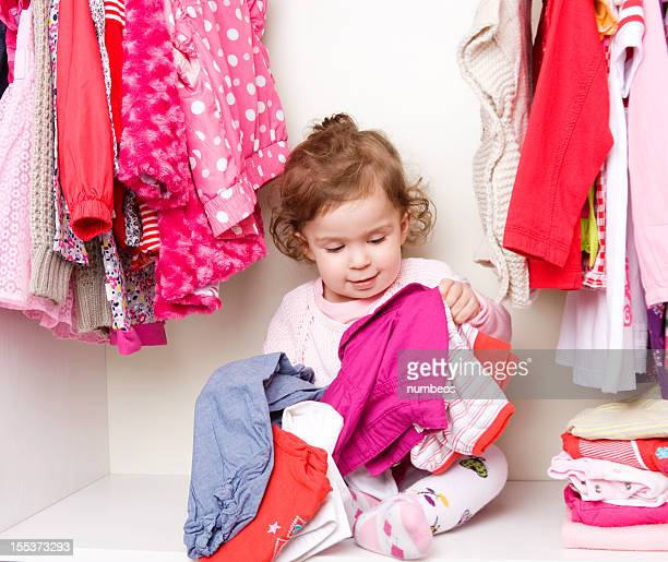 Baby girl choosing her clothes
