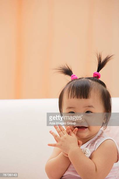 baby girl clapping hands and laughing, looking at camera - waist up stock pictures, royalty-free photos & images
