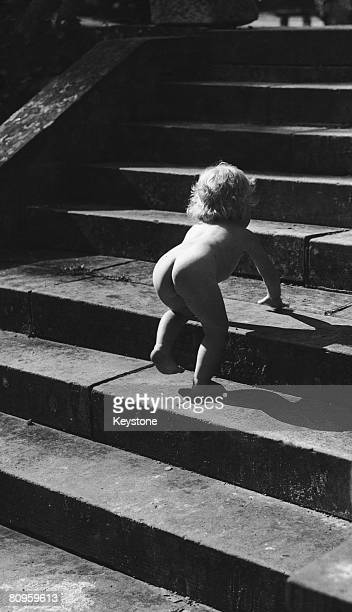 A baby girl climbing a flight of steps at a village fair in Wateringbury near Maidstone Kent circa 1935