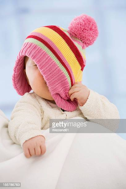 Baby girl covering face with hat, close up