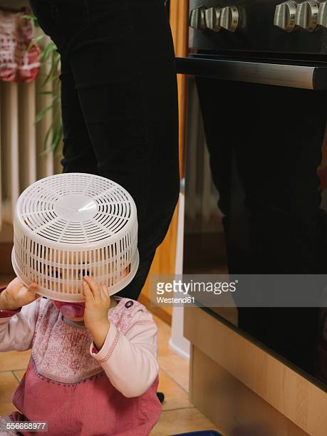 Baby girl covering head with strainer while mother is cooking