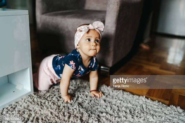 baby girl crawling on floor - hair band stock pictures, royalty-free photos & images
