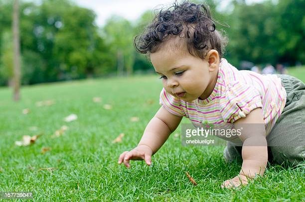 A baby girl crawling on grass and staring ahead