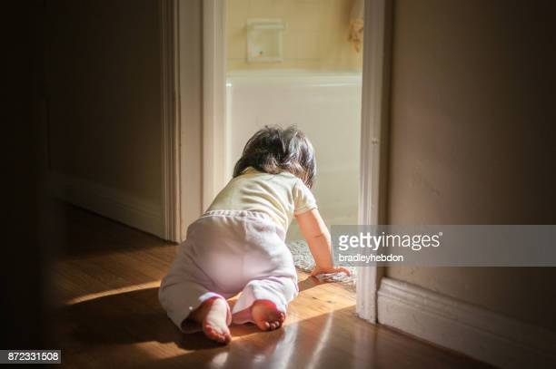 Baby girl crawling through passage in home