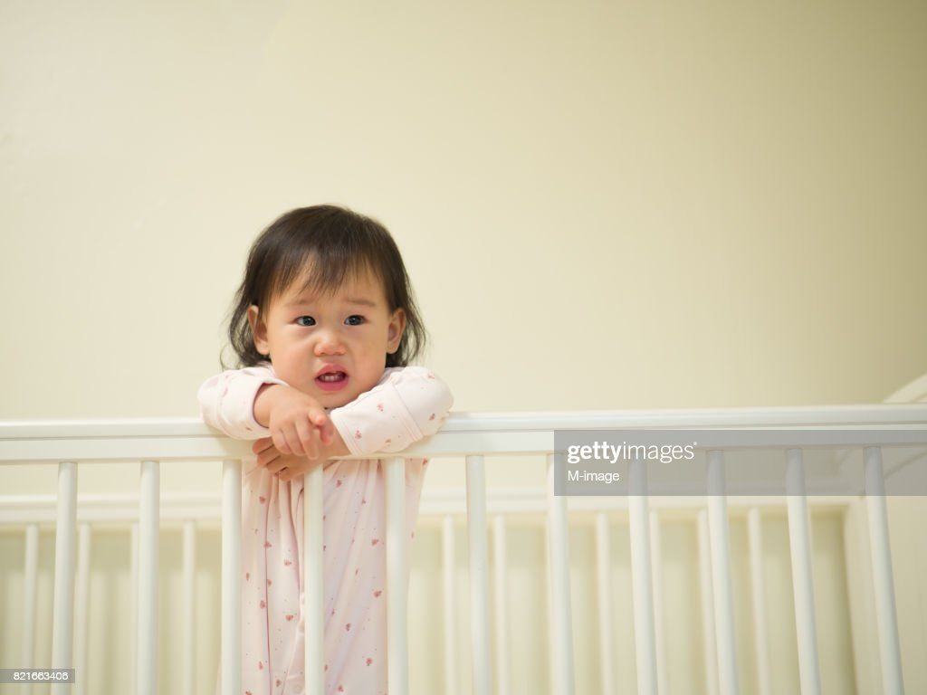 Baby girl crying in cot bed stock photo