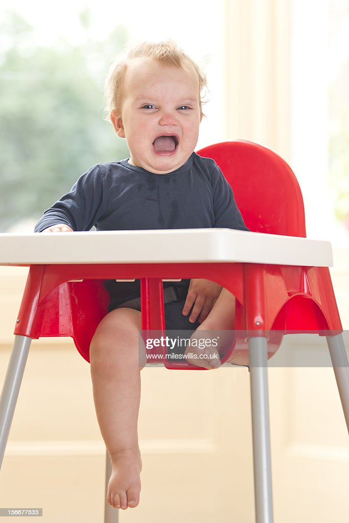 Baby girl crying in high chair : Stock Photo