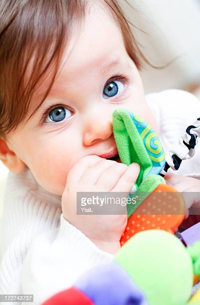 Baby girl discovering her textured toy with her mouth