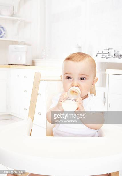 Baby girl (6-9 months) drinking bottle in high chair, close-up