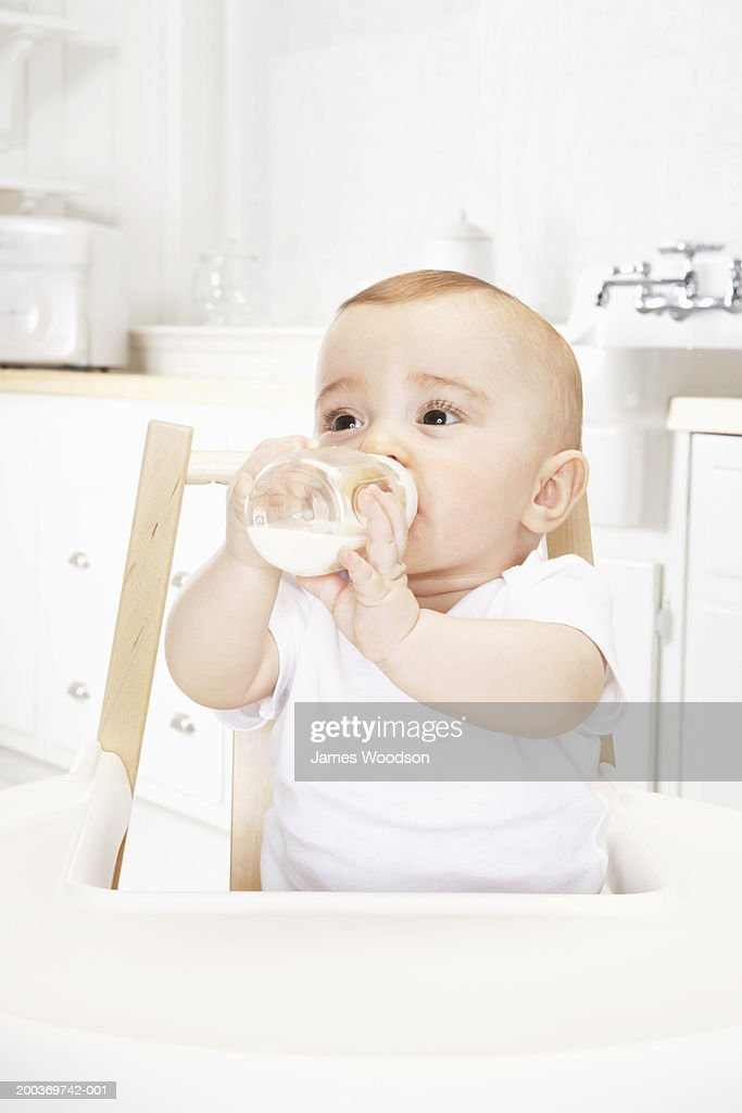 Baby girl (6-9 months) drinking bottle in high chair, close-up : Stock Photo