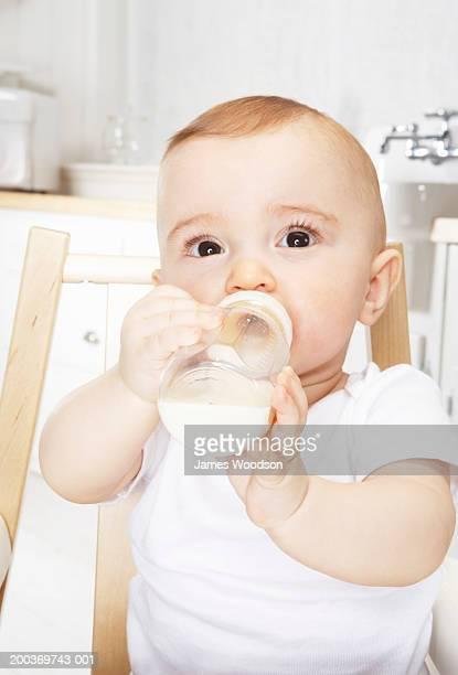 Baby girl (6-9 months) drinking bottle in high chair, portrait