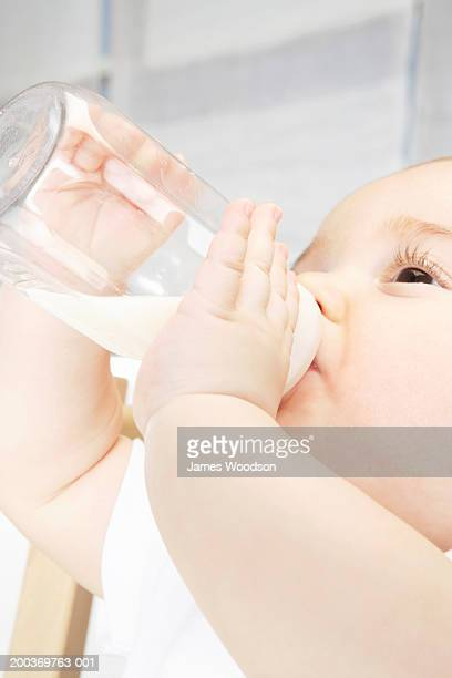 Baby girl (6-9 months) drinking bottle, side view, close-up