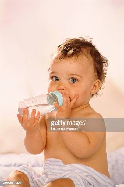 Baby girl (12-15 months) drinking from baby bottle, portrait