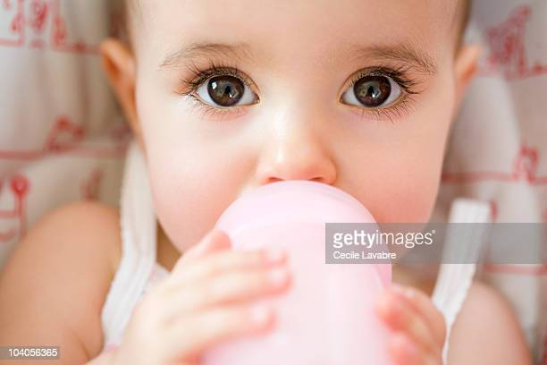 Baby girl drinking from bottle