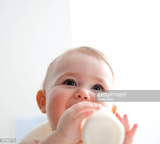 Baby girl (9-12 months) drinking from bottle.
