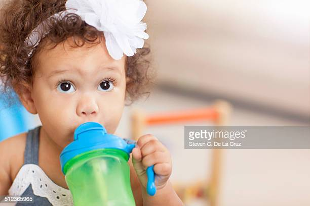 Baby girl drinking from sippy cup