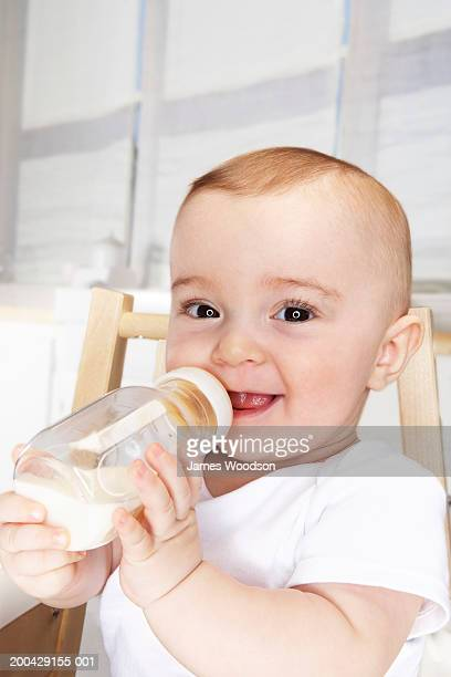 Baby girl (5-7 months) drinking milk from bottle, portrait