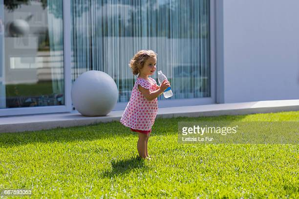 Baby girl drinking water from a bottle
