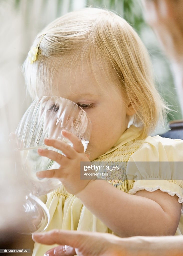 Baby girl (9-12 months) drinking water from wineglass : Foto stock
