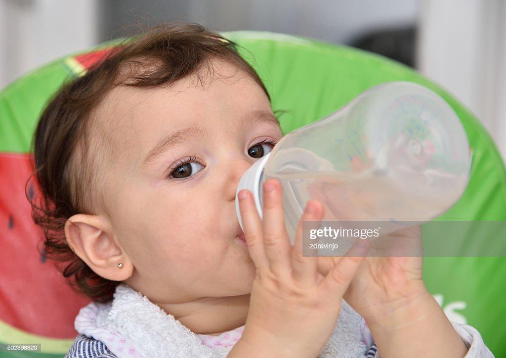 Baby girl drinking water : Stock Photo