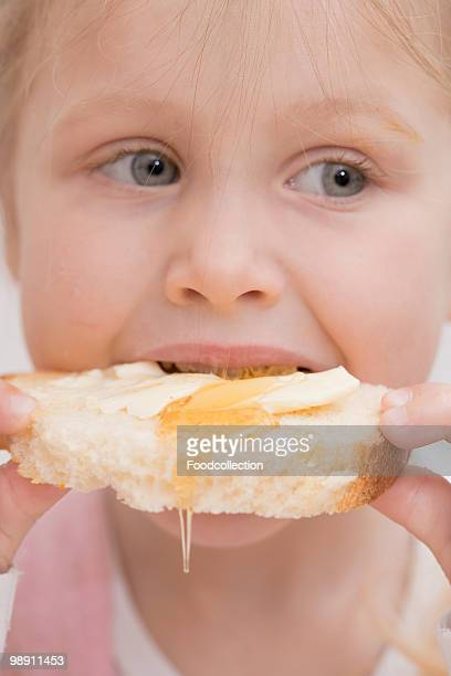 baby girl (12-23 months) eating bread with honey, close-up - 12 23 months stock pictures, royalty-free photos & images