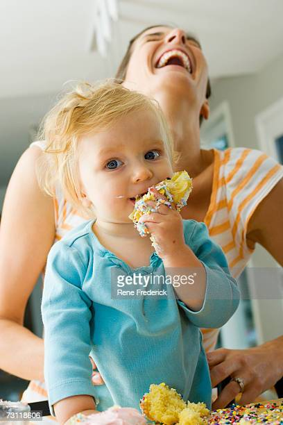 Baby girl (9-12 months) eating cake, held by mother, portrait