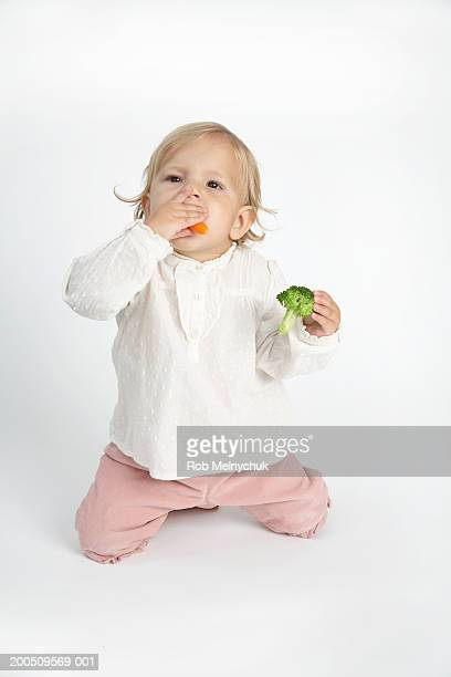 Baby girl (15-18 months) eating carrots and broccoli, looking up