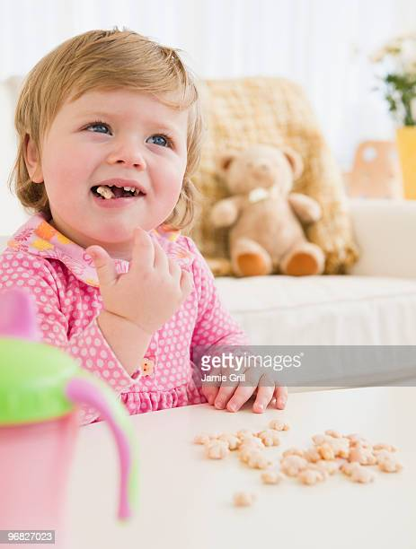 Baby girl eating cereal with fingers