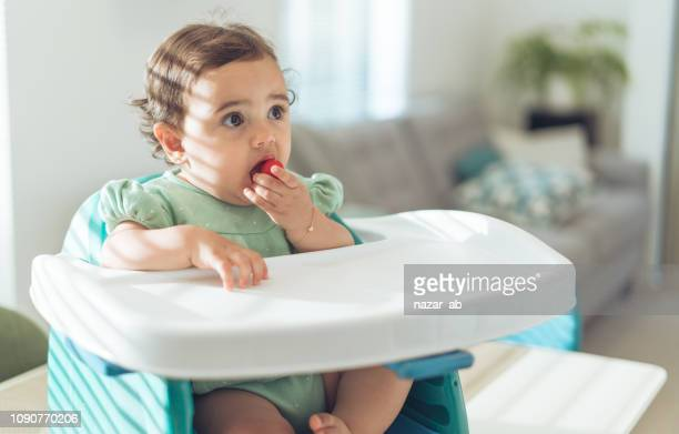 Baby girl eating cherry tomato.