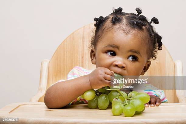 baby girl eating grapes - white grape stock photos and pictures