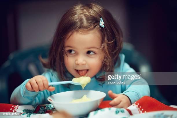 マッシュポテトを食べる女の赤ちゃん - ポリッジ ストックフォトと画像