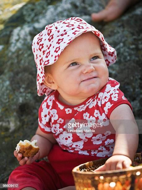 Baby girl eating outdoors, Sweden.
