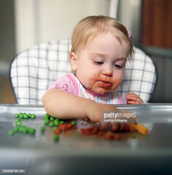 Baby girl (12-15 months) eating peas and pasta in high chair