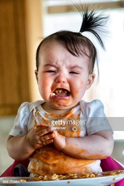 Niña comiendo espaguetis en silla y llorando