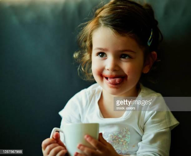 bambina che si gode il suo drink - innocenza foto e immagini stock